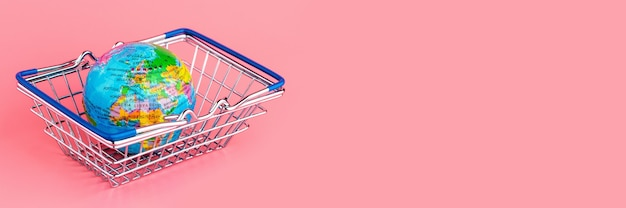 Small globe in a shopping cart on a pink background