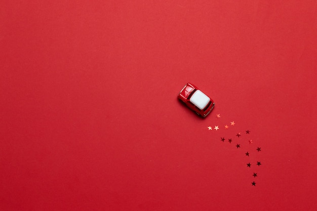 Small glossy toy car with golden star sparkles on a red background. holiday greeting card or banner.