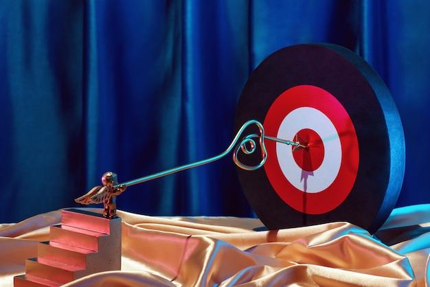 小さなゴールデンキューピッドは、バレンタインデーのコンセプトであるハートの矢印でターゲットをマークします。