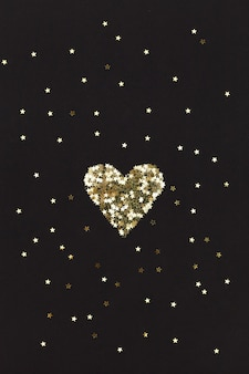 Small golden heart made of little stars on black background. christmas concept.
