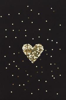 黒の背景に小さな星で作られた小さな金色のハート。クリスマスのコンセプト。