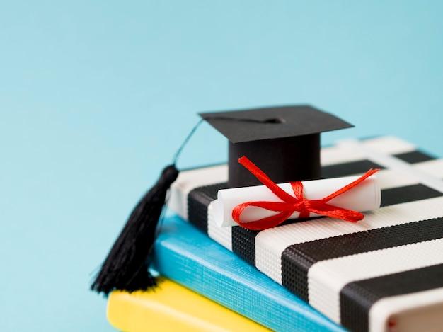 コピースペースと本の山に小さな卒業の帽子