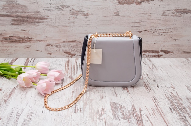 Small gray handbag with a price tag on a wooden background, pink tulips.