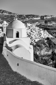 ギリシャのサントリーニ島の山岳海岸にあるフィラの町にある小さなギリシャの教会。白黒写真、風景