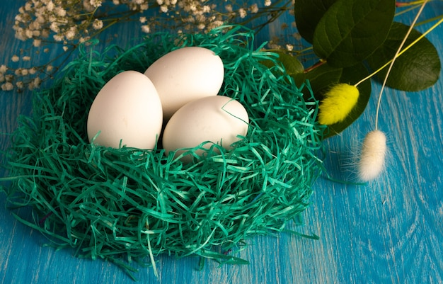 Small green nest with white eco eggs with flowers on light-blue wooden