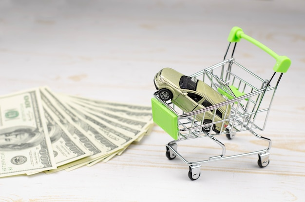 Small green shopping carttrolley with a toy car and 100 dollar banknotes on white wood