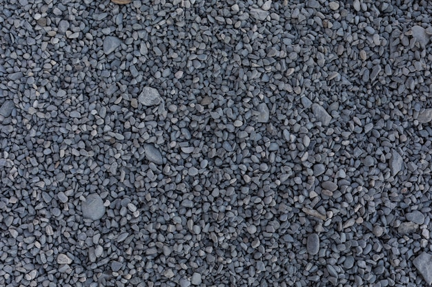Small grey stones for construction on the ground