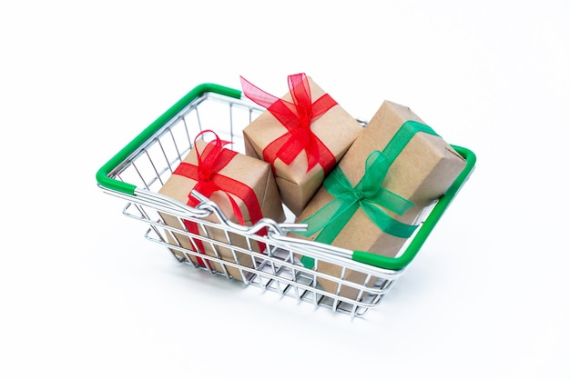 흰색 절연 된 표면에 선물 상자가있는 작은 식료품 바구니