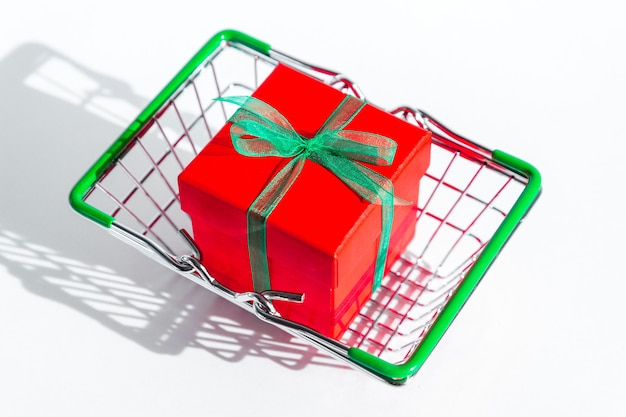 Small grocery basket with red gift box on white