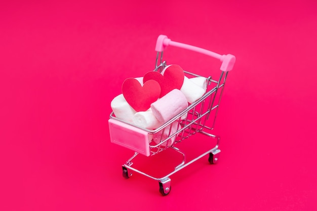 Small grocery cart full of sweet marshmallow candies. give gifts with love on valentine's day