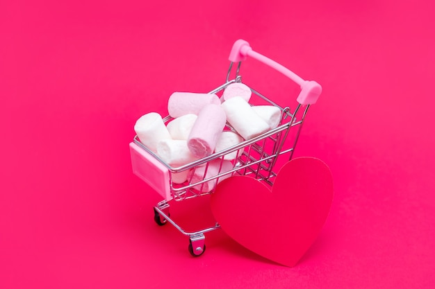 Small grocery cart full of sweet marshmallow candies. give gifts with love on valentine's day and