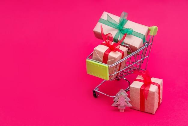 분홍색 표면에 크리스마스 선물 상자가있는 작은 식료품 카트