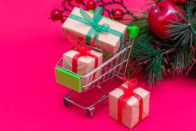 크리스마스 트리와 붉은 분홍색 표면에 선물 상자가있는 작은 식료품 카트