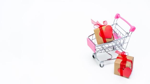 흰색 표면에 선물 상자가있는 작은 식료품 카트