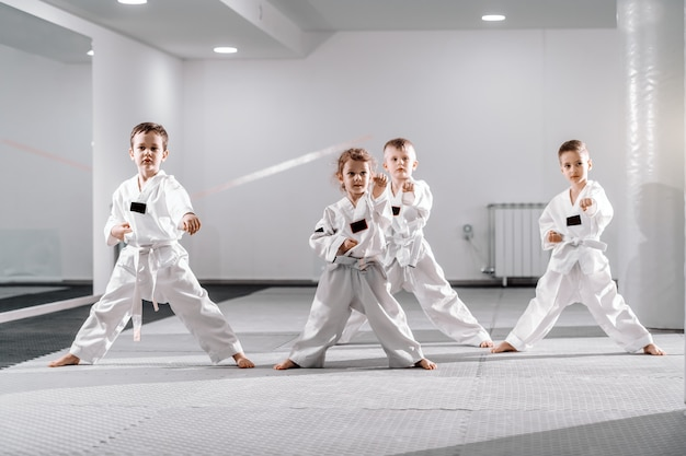 Small group of caucasian kids in doboks practicing taekwondo and warming up for treining while standing barefoot.