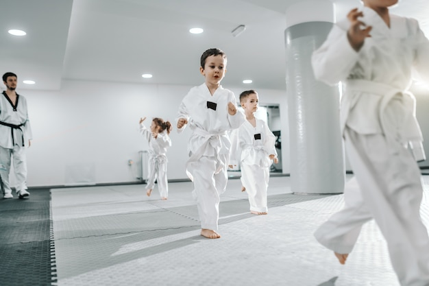 Small group of children having training at taekwondo class. all dressed in doboks. white background.