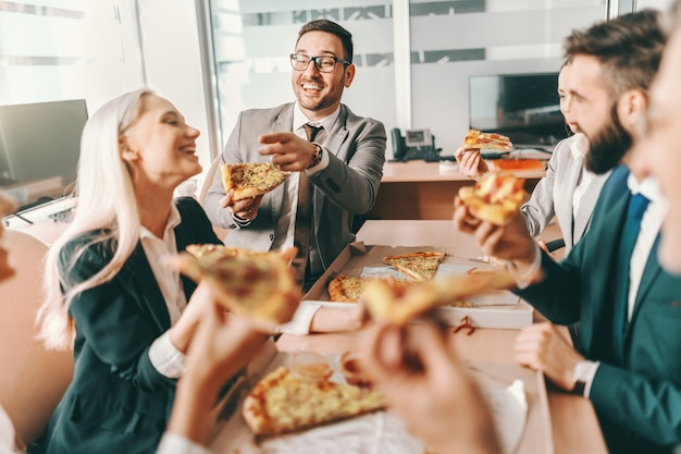 Small group of happy colleagues in formal wear chatting and eating pizza together for lunch. talent wins games, tut teamwork win championships.