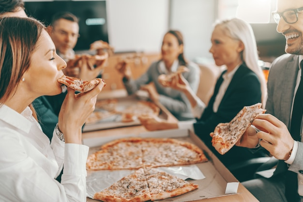 Small group of happy colleagues in formal wear eating pizza together for lunch.