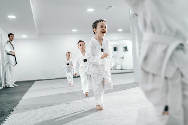 태권도 수업에서 훈련을받는 작은 그룹의 아이들. 모두 도복을 입고 있습니다. 흰 바탕.