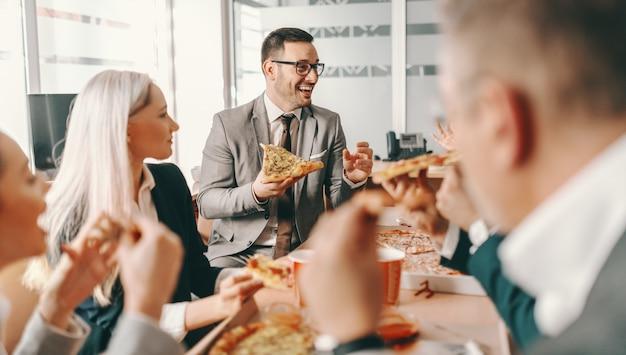 Небольшая группа счастливых коллег в официальной одежде болтает и вместе ест пиццу на обед. великие дела в бизнесе никогда не делаются одним человеком, их делает группа людей.