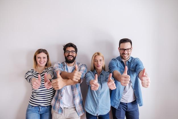 Малая группа людей давая большие пальцы руки вверх пока стоящ против белой стены. начать бизнес концепции.