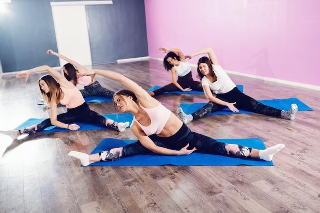 フィットネススタジオでマットの上に座っている間ストレッチ体操をしている女性の小さなグループ。