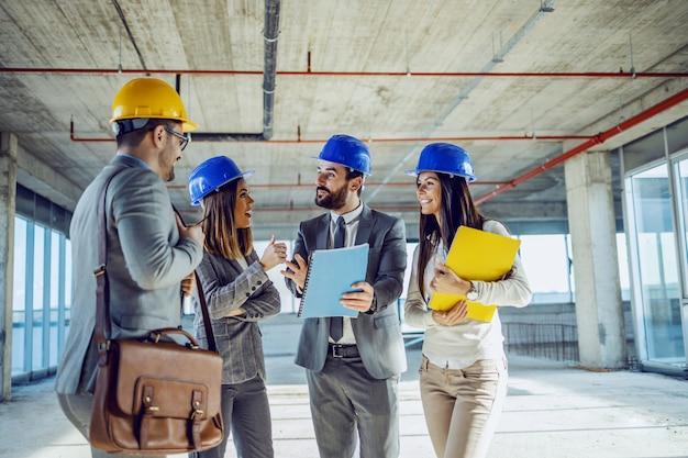 건축 과정에서 건물 내부에 서서 그 건물과 관련된 물건에 대한 신선한 아이디어에 대해 이야기하는 젊은 열심히 일하는 매우 의욕적 인 건축가의 소규모 그룹.