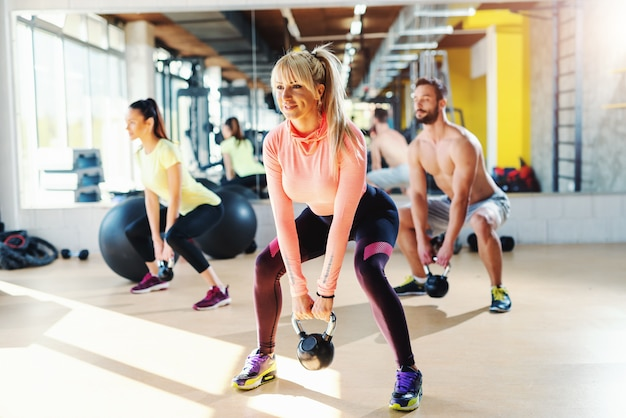 Small group of people with healthy habits swinging kettlebell. gym interior, mirror in background.male