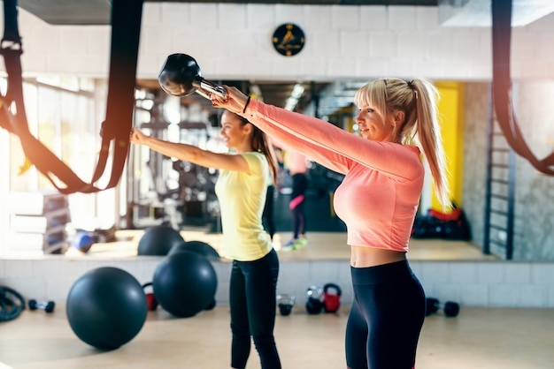 Small group of people with healthy habits swinging kettlebell. gym interior, mirror in background.