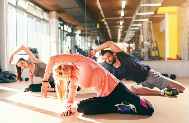 Small group of sporty people in sportswear doing side stretching while sitting on the gym floor. in background mirror.
