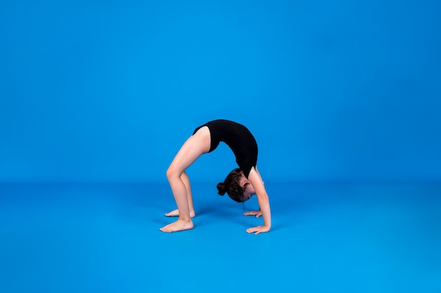 A small gymnast performs a bridge exercise on a blue background with a place for text