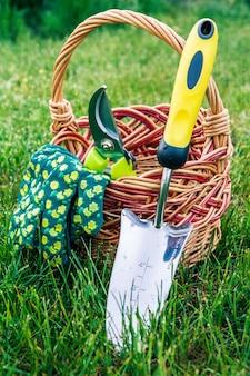 Небольшой ручной садовый шпатель, секатор и перчатки с плетеной корзиной в зеленой траве. садовые инструменты и оборудование