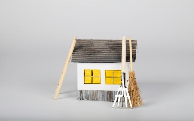 Небольшой бумажный домик ручной работы и садовые инструменты. крупным планом