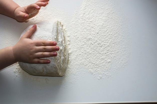小さな手で生地をこねる小さな子供が子供たちを支えるために生地を準備するいくつかの小麦粉小麦粉のダグを手に入れます...