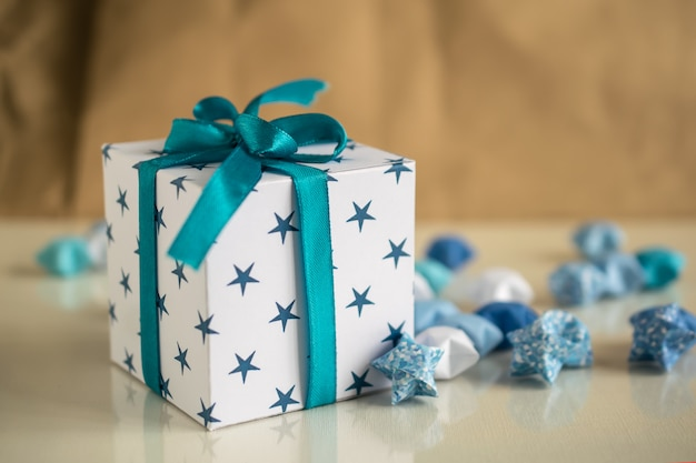 Small happy birthday gift box with paper stars and blue ribbon