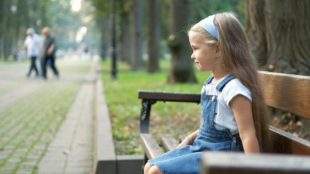 Маленькая счастливая детская девочка, сидящая на скамейке, отдыхая в летнем парке.