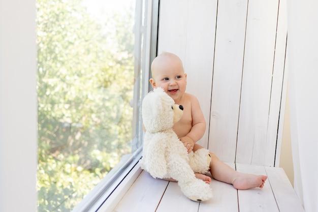 小さな幸せな子供はテディベアと一緒に窓辺に座っています。