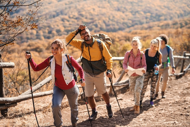 Small happy group of people hiking in the autumn while walking in the row.