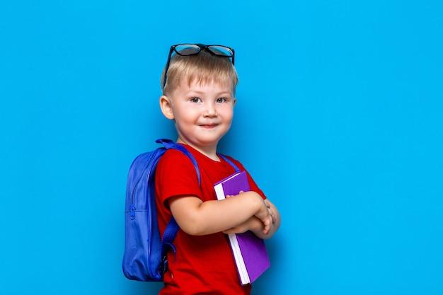 彼の頭に眼鏡をかけて小さな幸せな笑みを浮かべて男の子、手で予約、彼の肩にカバン。学校に戻る。学校へ行く準備ができて