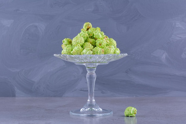 Un piccolo mucchio di popcorn canditi verdi su un supporto di caramelle di vetro su fondo di marmo. foto di alta qualità