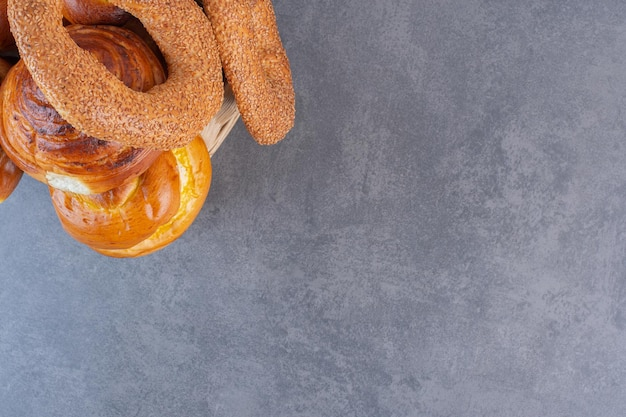 大理石の背景のバスケットにベーグルと甘いパンの小さなヒープ。高品質の写真