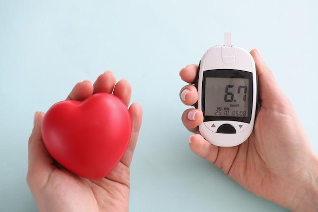 Маленькое сердце и глюкометр с индикаторами в руке