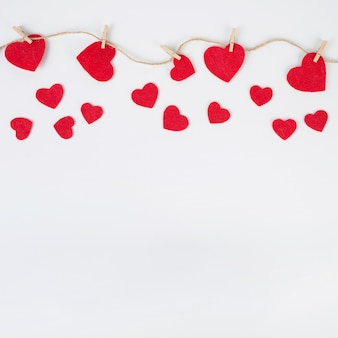 Small hearts pinned to rope on white table