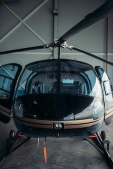 Маленький вертолет в ангаре, вертолет частной авиакомпании