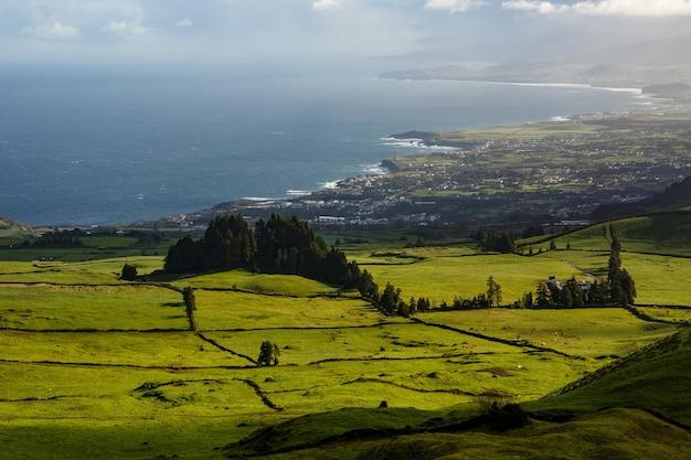 대서양 수준으로 떨어지는 신선한 녹색 들판과 초원으로 덮인 작은 언덕