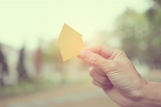 Small home model in hand with bokeh background, miniature house