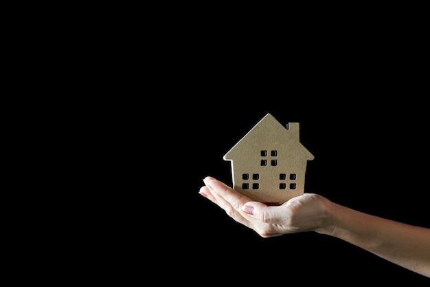 여자 손에 작은 집 모델. -집과 부동산 개념을 구입하십시오.