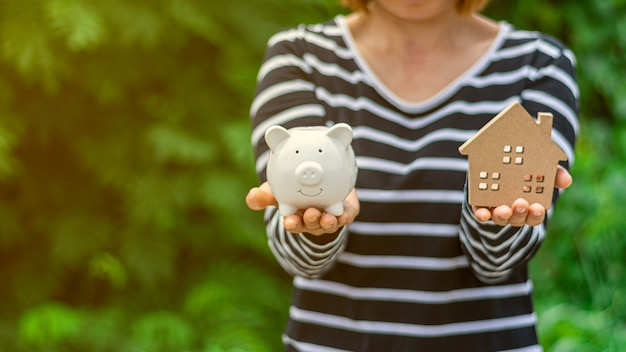 Small home model and a piggy bank in woman hand