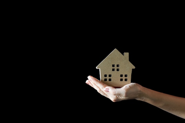 Small home model in woman hand. - buy house and real estate concept.