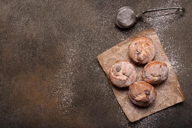 Маленькие домашние кексы с шоколадом и изюмом на деревянном столе, вид сверху